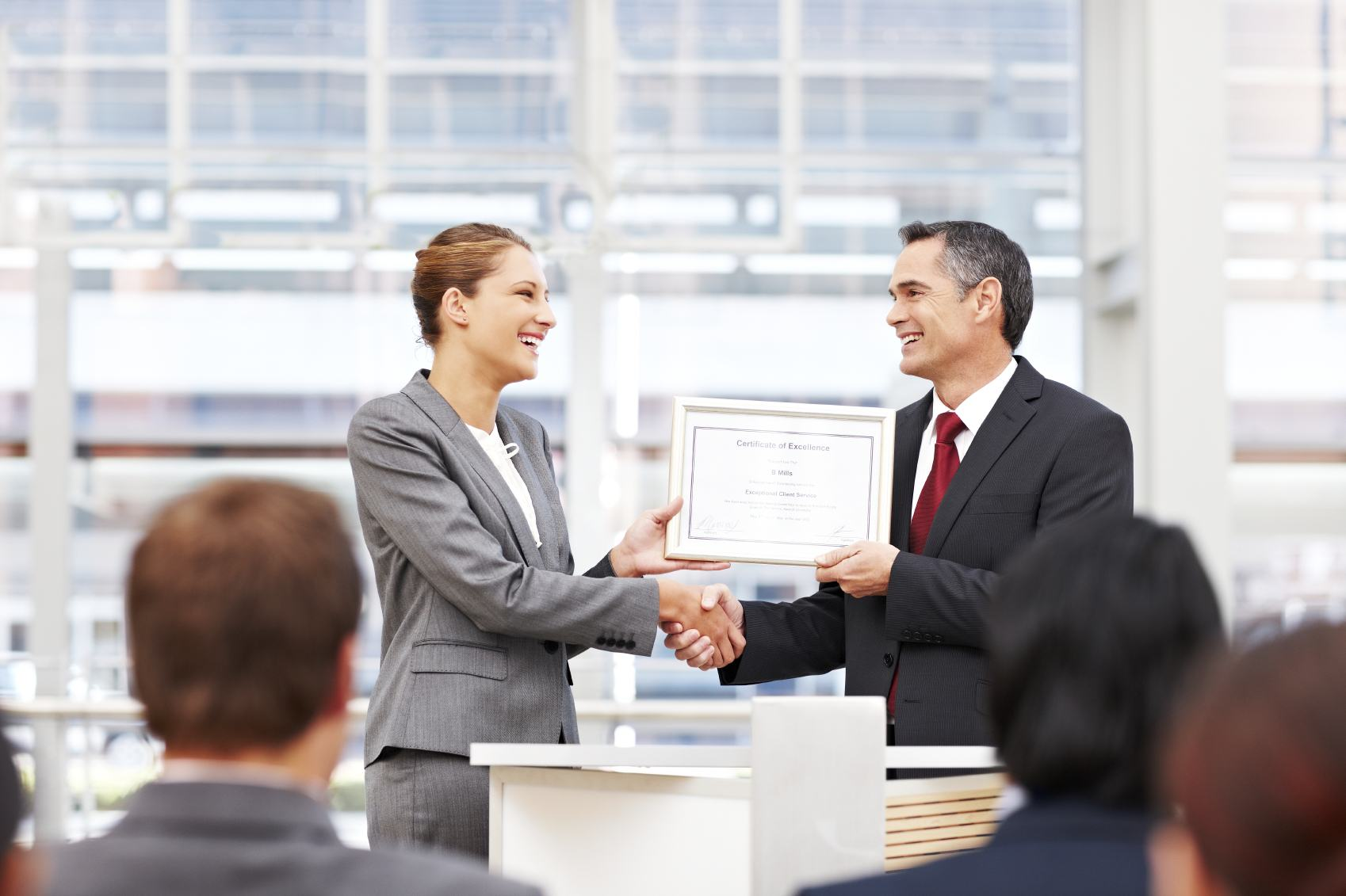 Businesswoman shakes the hand of a man giving her an award on stage. Horizontal shot.