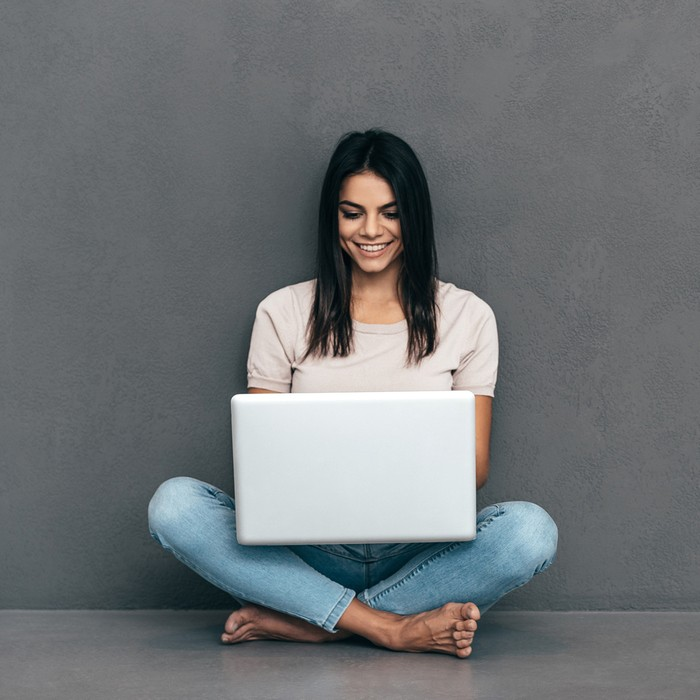 Attractive young woman in casual wear working on laptop and smiling while sitting barefoot and against grey background