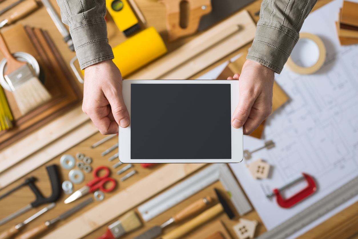 Male hands holding a digital tablet, work table with tools and project on background, home renovation and do it yourself concept