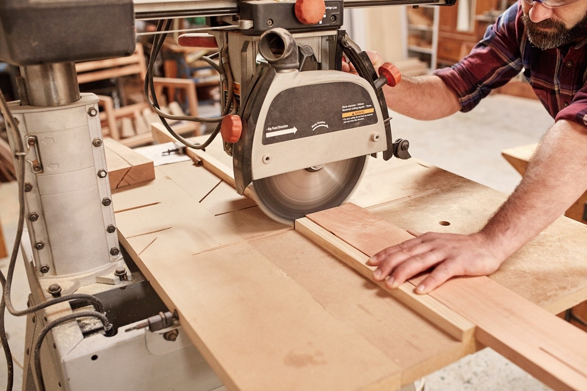 Cropped shot of a carpenter using a radial arm circular saw to cut a plank of wood, in his woodwork studio